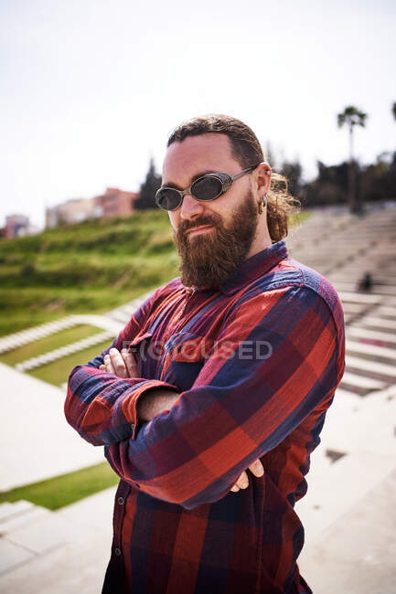 Self assured adult hipster male with crossed arms in checkered shirt and sunglasses looking at camera in city — стоковое фото