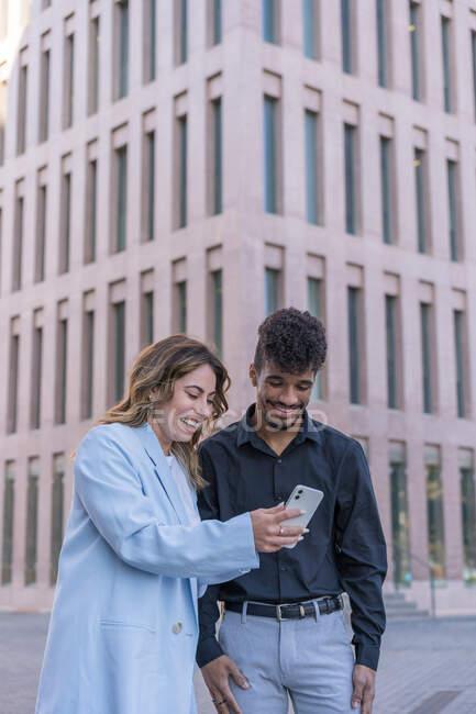 Homem e mulher africanos étnicos de corpo inteiro em roupas casuais inteligentes compartilhando smartphone em pé na rua de paralelepípedos contra o edifício contemporâneo — Fotografia de Stock