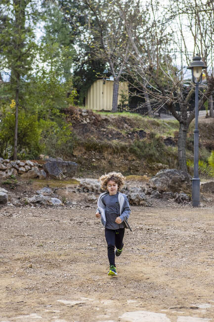 Child in casual apparel running on rough land against hill with trees in daylight — Foto stock