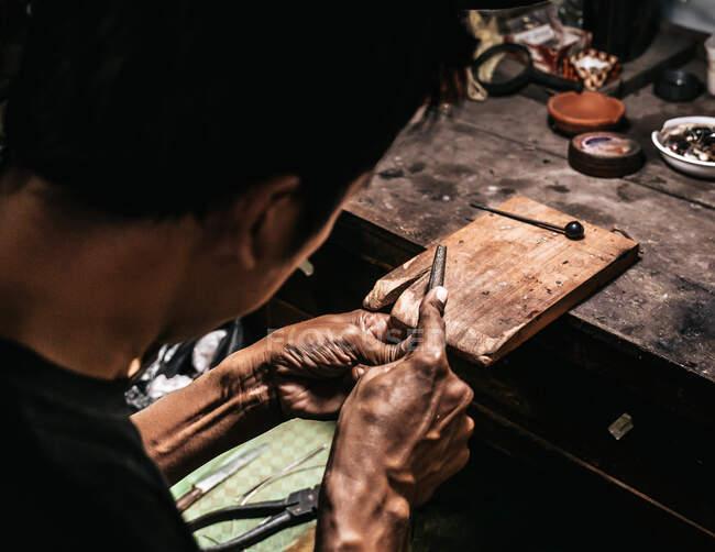 Von oben kam unkenntlich konzentrierter ethnischer älterer Juwelier in lässiger Kleidung und Brillenschärfungsinstrumenten bei der Arbeit am Holztisch in der traditionellen Werkstatt — Stockfoto