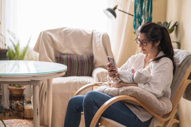 Mamma che abbraccia anonimo neonato mentre usa il cellulare nella stanza della casa nella giornata di sole — Foto stock