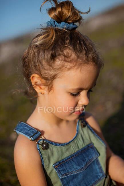 Encantada niña adorable en overoles de pie en el prado y mirando hacia abajo - foto de stock