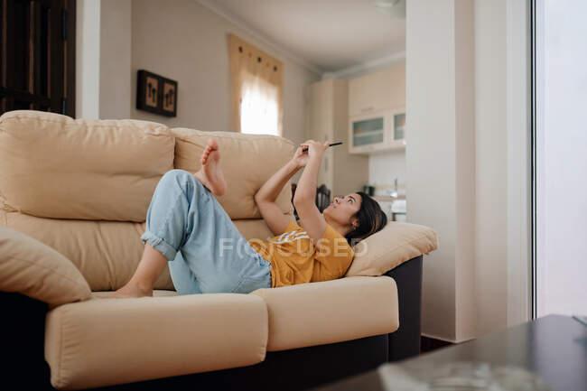 Вид сбоку молодой женщины, которая читает текст на мобильном телефоне, лежа на диване в гостиной — стоковое фото