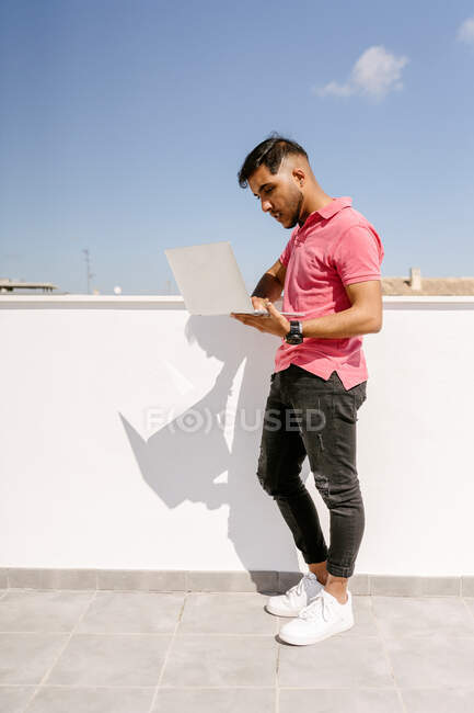 Side view of focused young ethnic male freelancer with dark hair in trendy outfit standing on terrace and using laptop during distance work — Stock Photo