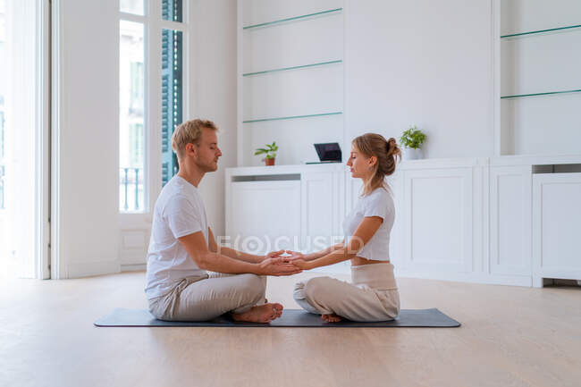 Side view of peaceful couple sitting in Lotus pose and holding hands while practicing yoga together and meditating with closed eyes — стоковое фото