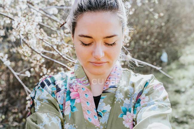 Jovem fêmea sorridente com olhos fechados apreciando flor de árvore florescente no jardim à luz do sol no fundo borrado — Fotografia de Stock