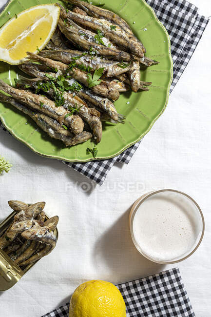 From above of delicious fried anchovies served on plates with lemon and placed on white table with glass of beer — Fotografia de Stock