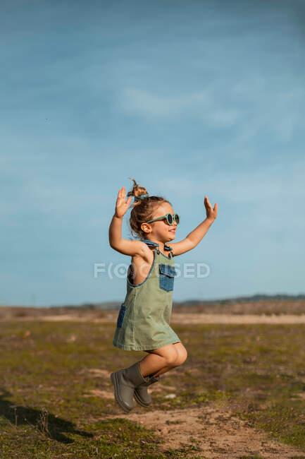Seitenansicht des zufriedenen kleinen Mädchens in Overalls und Sonnenbrille, das mit ausgestreckten Armen über die Wiese springt und den Sommer an sonnigen Tagen in der Natur genießt — Stockfoto
