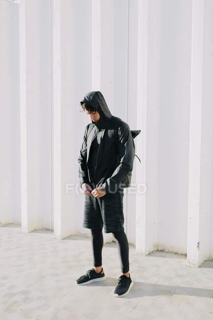 Lunghezza intera dell'atleta maschile che indossa abbigliamento sportivo total black con cappuccio giacca a vento in piedi su strada con zaino — Foto stock
