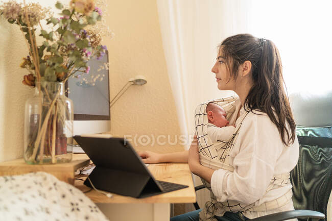 Mãe adulta sentada na mesa trabalhando no computador desktop e tomando notas no caderno enquanto segurava a criança na mesa durante o dia — Fotografia de Stock