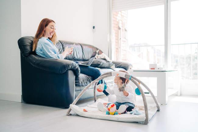 Зосереджена молода мати в повсякденному одязі, переглядає смартфон і нетбук сидячи на дивані біля милого малюка, граючи з іграшками на підлозі у вітальні. — стокове фото