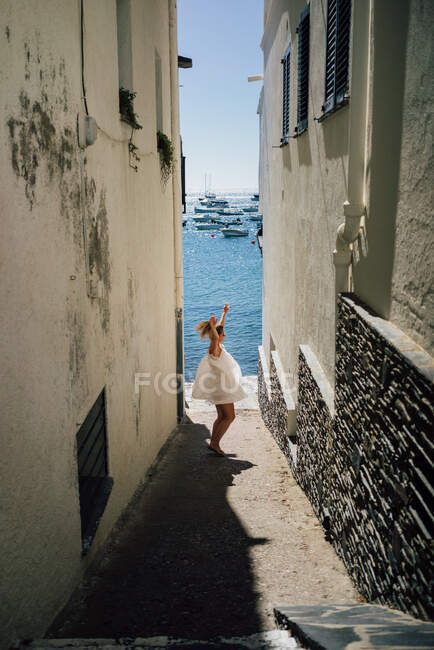 Side view of anonymous carefree female tourist with raised arms dancing on narrow street between old buildings in city - foto de stock