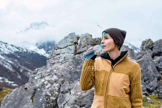 Femme en vêtements chauds debout sur la haute gamme de sommets de l'Europe et de l'eau potable — Photo de stock