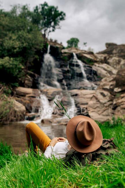 Anonimo viaggiatore maschio in cappello rilassante sul lungolago lussureggiante e godendo di una rapida vista a cascata nella natura estiva — Foto stock