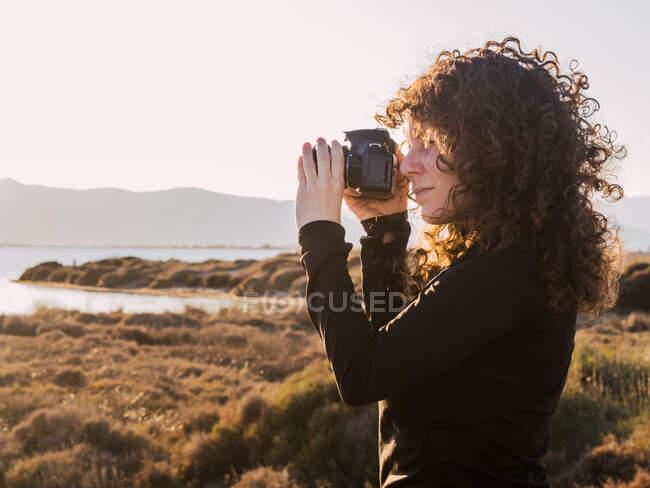 Side view of focused young curly haired ethnic female traveler taking pictures on photo camera while standing near sea in sunny evening — Foto stock
