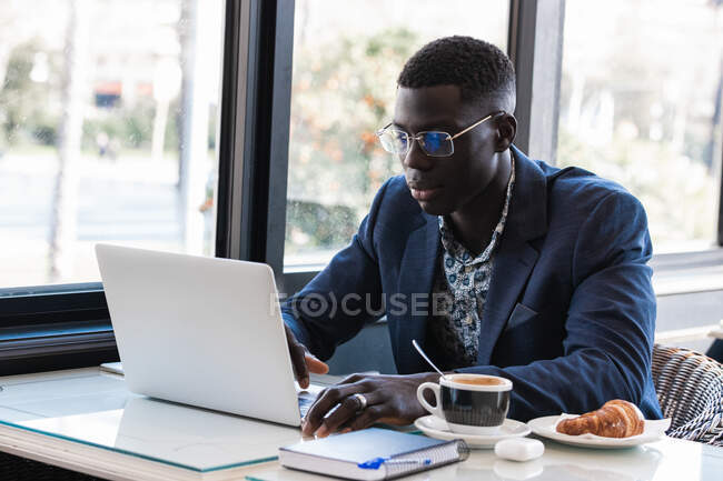 Serious African American male entrepreneur sitting at table in cafe and browsing netbook while working on project remotely — Stock Photo