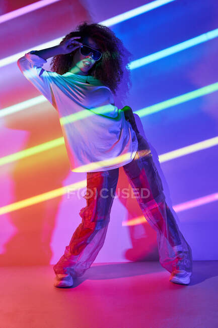 Full body stylish confident female dancer standing in neon lights and touching sunglasses in dancing studio — Stock Photo