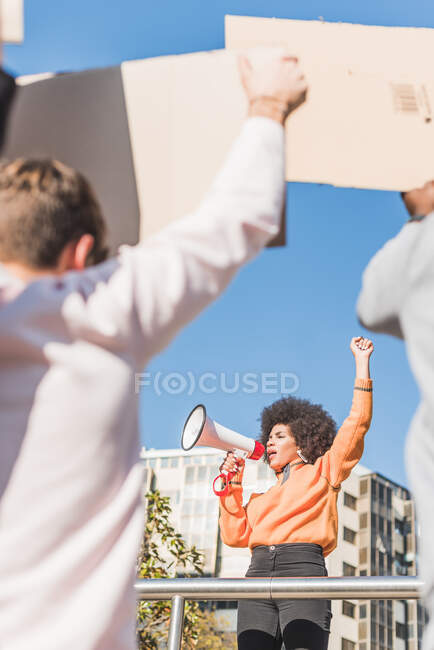 African American female social justice warrior with speaker against crop anonymous multiracial people with placards fighting for human rights in town — стокове фото