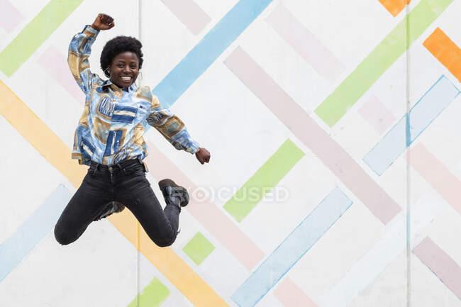 Повний набір щасливої молодої афроамериканської жінки в стильному вбранні стрибає на міському фоні, дивлячись на камеру — стокове фото