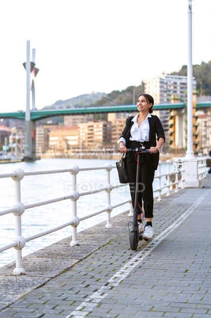 Задоволена етнічна жінка-підприємець у формальному одязі їздить на електричному скутері, озираючись на дорогу в місті. — стокове фото