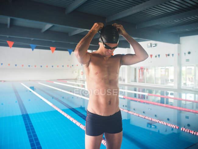 Deportista en traje de baño y gorra con las manos detrás de la cabeza preparándose para el entrenamiento contra la piscina con carriles en la construcción - foto de stock