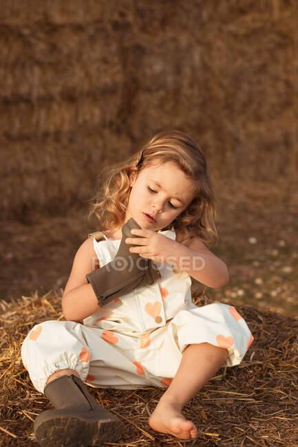 Criança curiosa adorável em macacão sentado no palheiro e olhando para botas à noite no campo — Fotografia de Stock