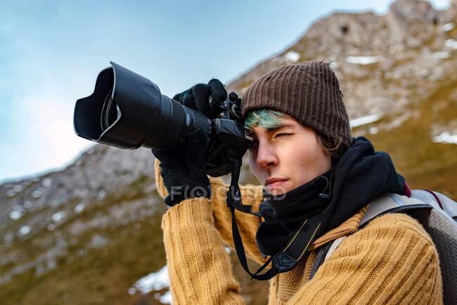 Vista laterale turista femminile con zaino utilizzando fotocamera fotografica durante le riprese sorprendente natura di Cime d'Europa durante il viaggio — Foto stock