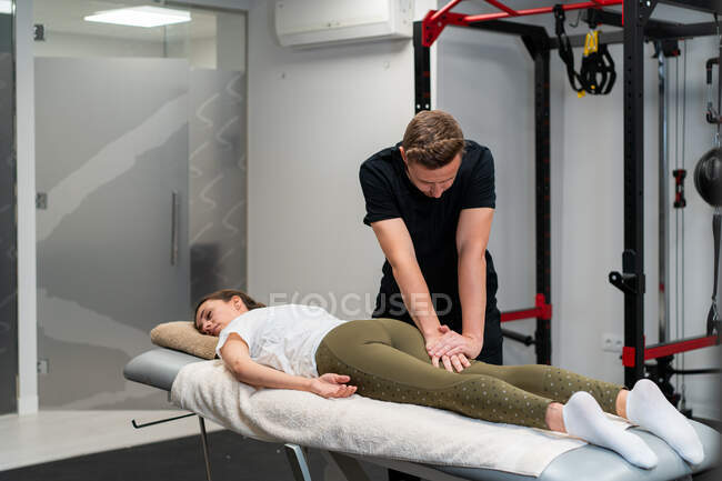Unshaven fisioterapeuta masculino massageando perna de mulher na cama durante o procedimento médico no hospital — Fotografia de Stock