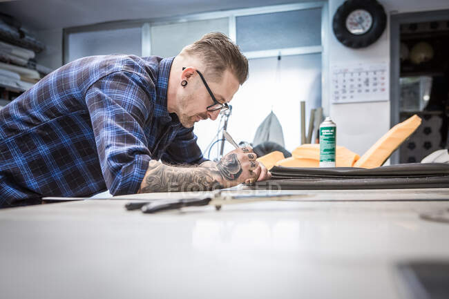 Side view of concentrated male master making marking on piece of leather while creating upholstery for motorcycle seat in workshop — Stock Photo
