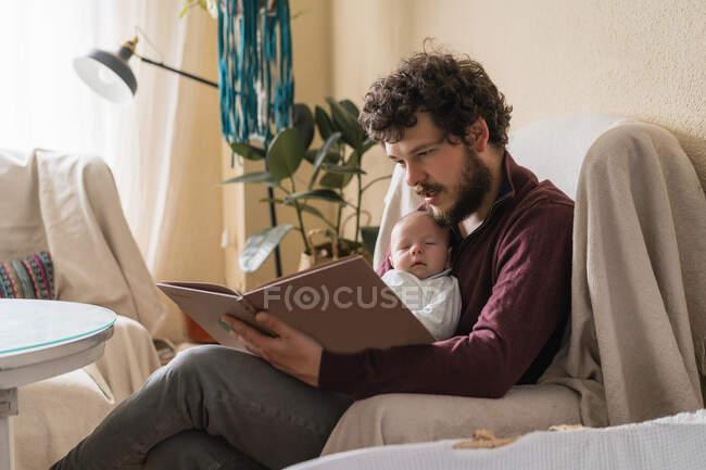 Pai barbudo com adorável criança leitura livro enquanto sentado com pernas cruzadas em poltrona em casa — Fotografia de Stock