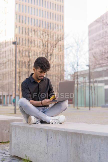 Cuerpo completo joven hombre étnico sentado en el banco de bloques de hormigón y compras en línea con tarjeta y portátil en el centro de la ciudad - foto de stock