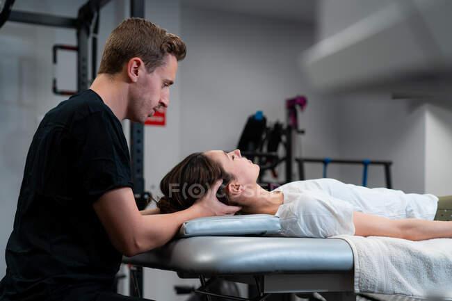 Vista lateral del fisioterapeuta masculino sin afeitar masajeando el cuello de la mujer con los ojos cerrados en el hospital - foto de stock