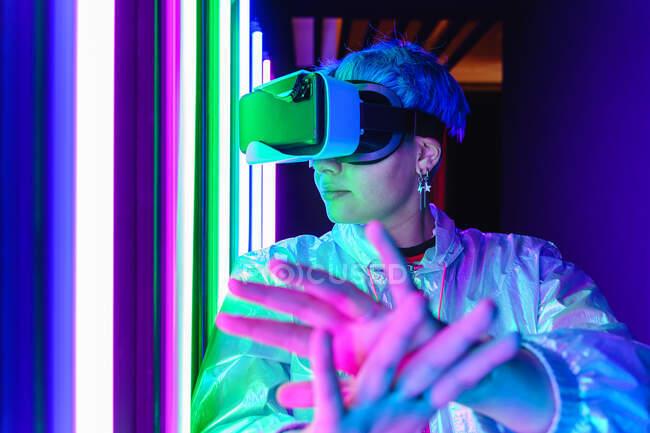 Mujer anónima en auriculares modernos con brazos extendidos explorando la realidad virtual en luz púrpura - foto de stock