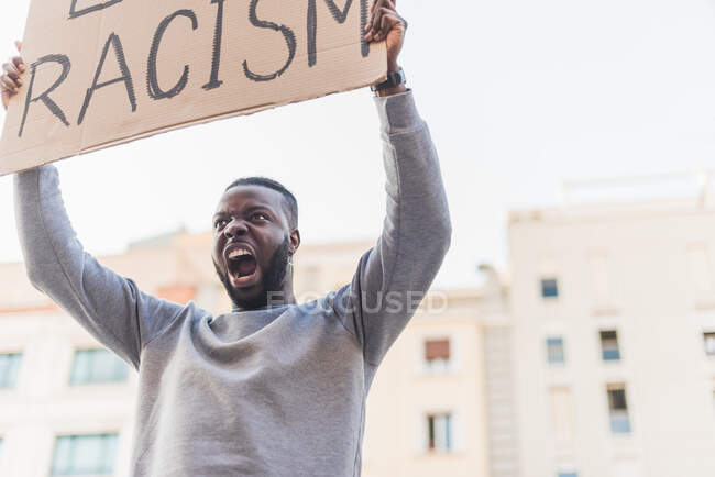 Low angle of African American male activist with poster screaming on city street during Black Lives Matter protest — Fotografia de Stock