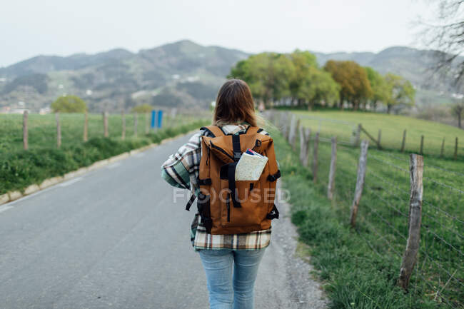 Back view of anonymous female hiker with route map in rucksack strolling on countryside roadway against mount - foto de stock