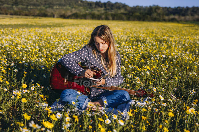 Young hipster woman sitting on a meadow in the countryside writing songs on notebook and playing guitar during summer sunlight. — Stock Photo