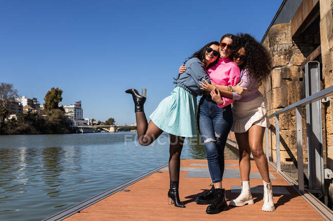 Full body cheerful multiethnic female friends in casual outfits embracing each other on city waterfront and looking at camera with smiles on sunny summer day — стокове фото
