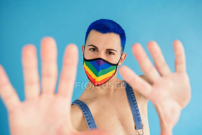 Юний тонкий гомосексуальний чоловік з пофарбованим синім волоссям у денімському костюмі на голому торсі і маску обличчя в кольорах веселкового прапора, що стоять на синьому тлі і дивляться на камеру. — стокове фото