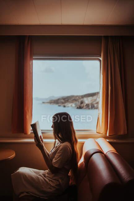 Нерозбірлива жінка в сонячному одязі читає книжку, сидячи на затишному дивані в поромному човні і пливучи на хвилястому мальовничому морі в Греції. — стокове фото