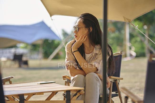 Hermosa mujer asiática étnica en gafas de sol sentada en la mesa mientras disfruta de un momento de relax en la zona de acampada durante las vacaciones mirando hacia otro lado - foto de stock