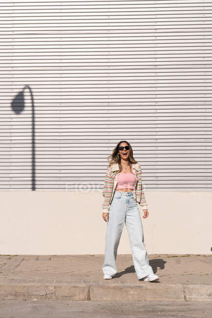 Cheerful female in sunglasses and stylish apparel standing on tiled walkway against wall in town — Stock Photo
