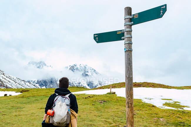 Visão traseira do mochileiro feminino em pé contra o pólo no pico da Europa — Fotografia de Stock