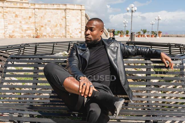 Серйозний афроамериканець у шкіряній куртці сидить на вулиці з пересіченими ногами і відводить погляд у думках — стокове фото