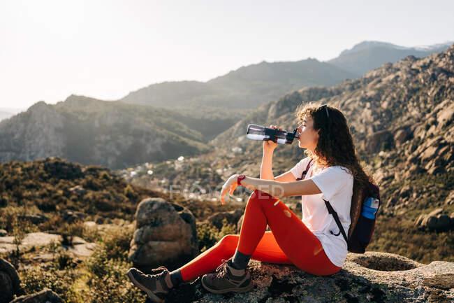 Vista laterale della giovane escursionista stanca con capelli ricci scuri in abbigliamento casual e zaino acqua potabile mentre riposa sulla pietra durante il trekking in valle montuosa — Foto stock