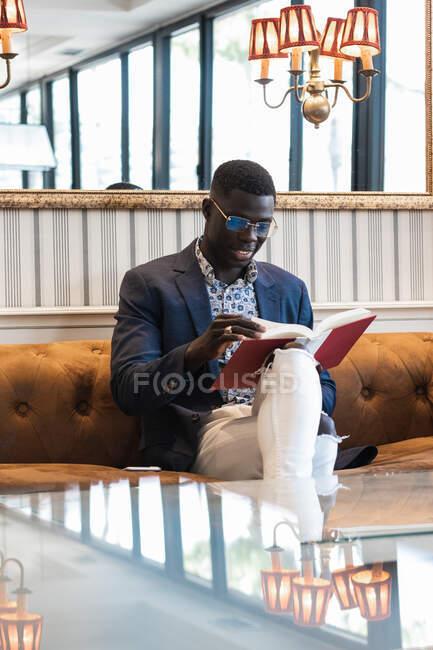 Empreendedor masculino afro-americano focado em roupas elegantes sentadas no sofá em café de luxo e livro de leitura — Fotografia de Stock