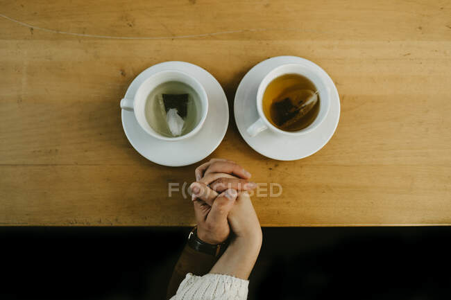 Top view of crop unrecognizable couple holding hands while sitting at table with cups of hot tea — Stock Photo