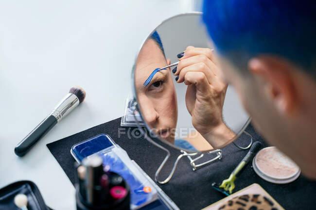 Багатий спокійний самець з синім волоссям використовує дреґ і відбиває кругле дзеркало в роздягальні. — стокове фото