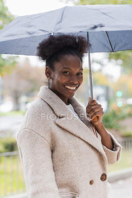 Молода африканська жінка в теплому пальто стоїть з парасолькою на сучасній вулиці міста і дивиться на камеру — стокове фото
