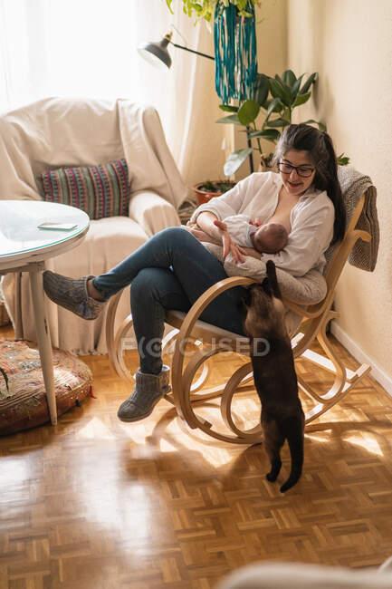 Мама в окулярах смокче анонімну дитину на м'якій подушці, сидячи в хатній кімнаті вдень. — стокове фото