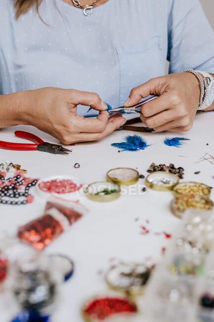 Vista lateral do designer de culturas com pinça fazendo bijouterie decorativo sentado à mesa com diferentes cristais e lantejoulas — Fotografia de Stock